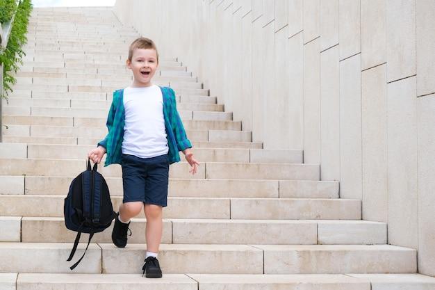 Школьник с рюкзаком в руке на улице по дороге в школу спускается по лестнице. обратно в школу.