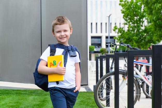 Школьник с книгой в руке на улице по дороге в школу. обратно в школу.