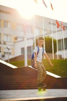 Школьник с коньком и рюкзаком