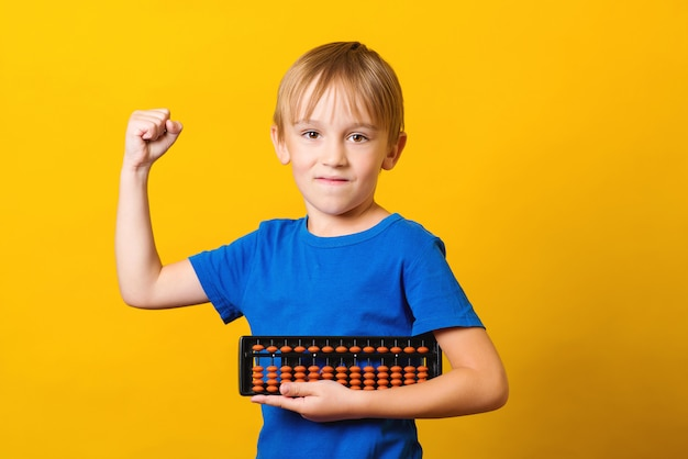 黄色の背景にそろばんの男子生徒。暗算学校での子供の研究。
