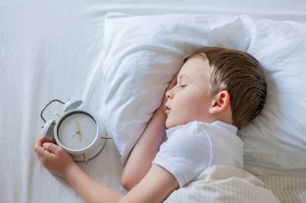 침대에서 자 고 알람 시계와 모범생입니다. 아침.