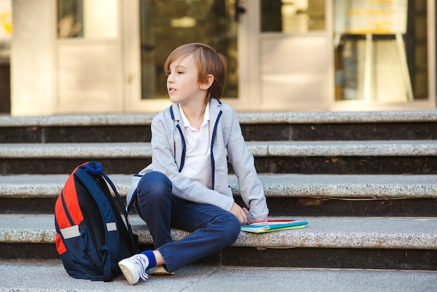 Schoolboy with backpack and books sitting on the stairs.