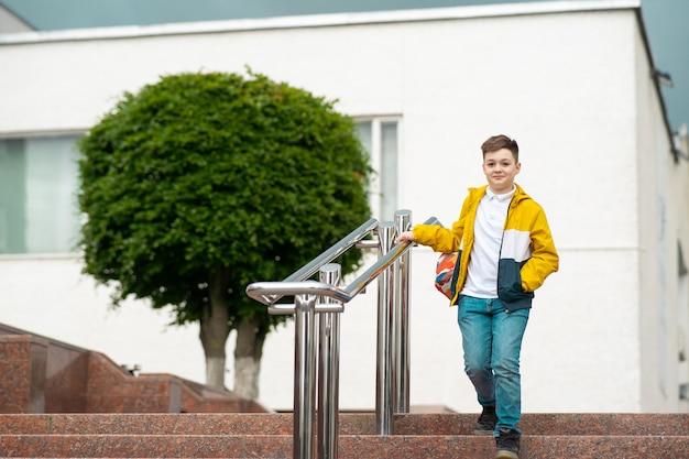Школьник с рюкзаком спускается из школы по лестнице.