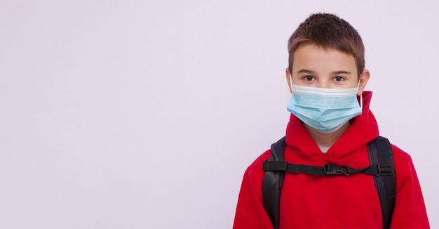 Schoolboy with a backpack behind his back wearing a medical mask