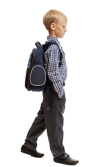 A schoolboy with a backpack is walking.
