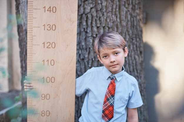 Schoolboy with big ruler standing on wooden background. farewell bell. day of knowledge.