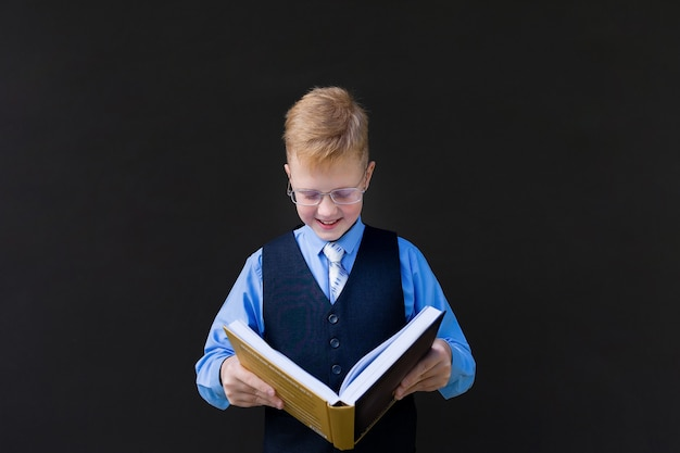 The schoolboy with a book on a black background
