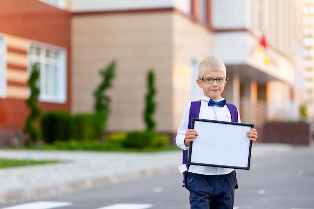 Школьник в очках стоит у школы и держит табличку с белой простыней
