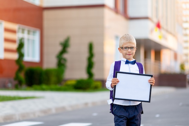 Schoolboy with glasses stands at the school and holds a sign with a white sheet