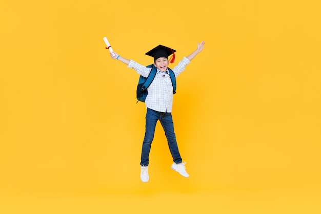 Школьник с кепкой выпускника улыбается и прыгает
