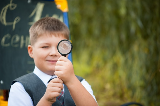 A schoolboy with a magnifying glass getting ready for school