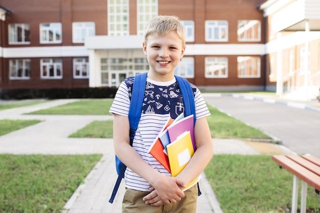 Школьник с тетрадями и рюкзаком