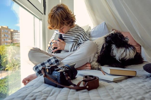 Школьник со старой фотоаппаратом возле цвергшнауцера на кровати