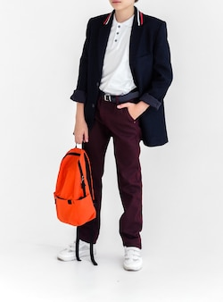 A schoolboy with an orange bag in his hands stands on a white background in a school uniform  trouse...