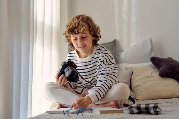 Школьник с фотоаппаратом, писать в блокноте на кровати