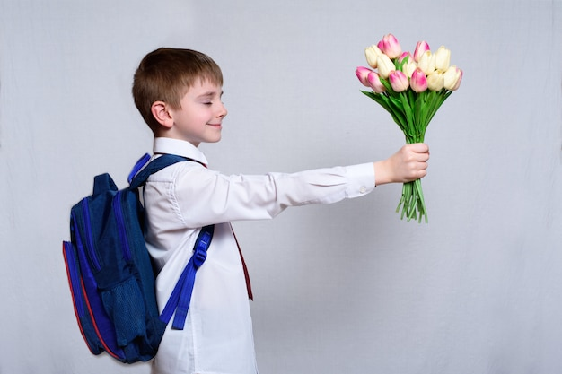 Schoolboy with a school bag gives a bouquet of tulips as gift for mothers day