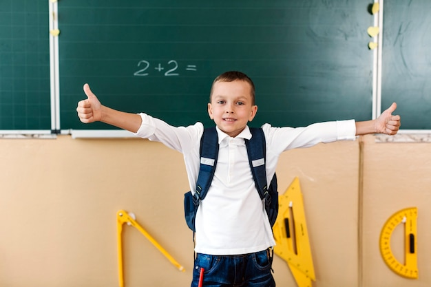 Schoolboy with thumbsup and hands apart