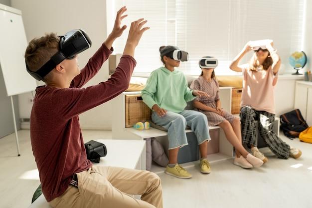 レッスンでの仮想プレゼンテーション中に大きなディスプレイに触れるヘッドセットを持つ男子生徒
