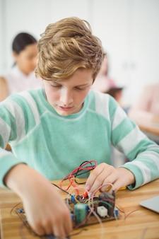 教室で電子プロジェクトに取り組んでいる少年
