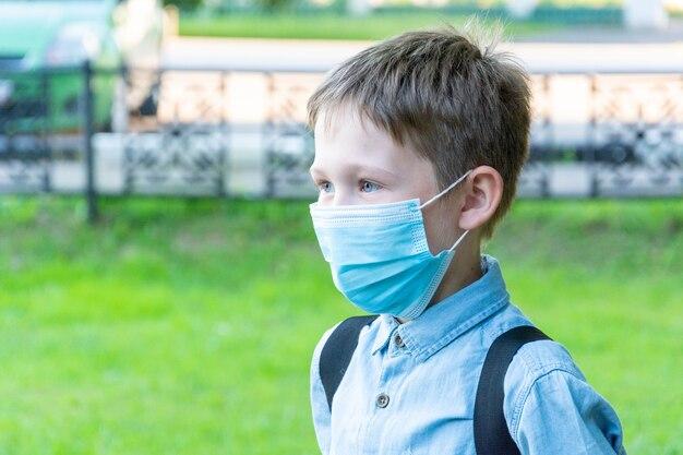 Школьник лет в медицинской маске с рюкзаком на зеленом фоне