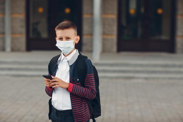 Школьник молодой мальчик стоит с мобильным телефоном и медицинской маской, стоя в школе