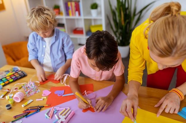 先生の近くの男子生徒。切り抜きと絵を描いている間、先生の近くに立っている2人の男子生徒