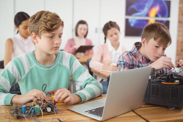 教室で電子プロジェクトに取り組んでいる男子生徒