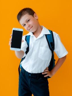 학생 소년은 휴대 전화 격리 된 노란색 배경을 보유하고 있습니다. 스마트폰은 검은색 디스플레이로 닫힙니다. 자녀 보호는 스마트폰 앱입니다. 어린이와 현대 기술.