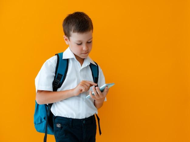 학생 소년은 휴대 전화 격리 된 노란색 배경을 보유하고 있습니다. 스마트폰은 검은색 디스플레이로 닫힙니다.