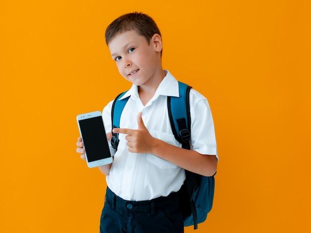 학생 소년은 휴대 전화 격리 된 노란색 배경을 보유하고 있습니다. 검은색 디스플레이 포인팅 제스처로 스마트폰을 닫습니다. 자녀 보호 스마트폰 앱. 어린이 현대 기술.
