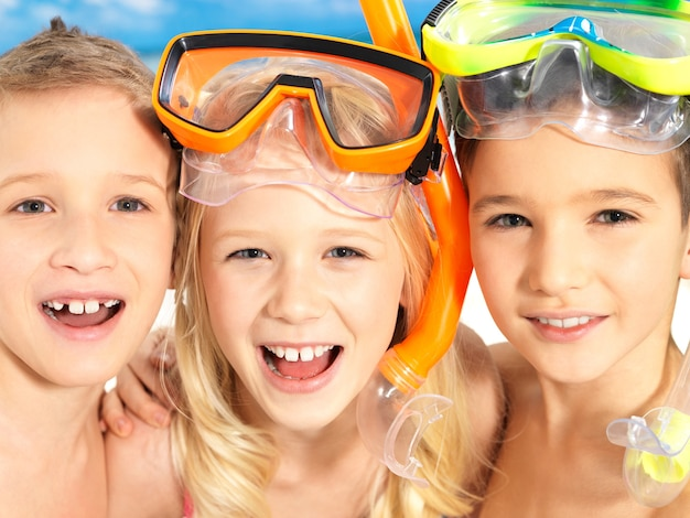 Schoolchild kids standing together in bright color swimwear with swimming mask on head .