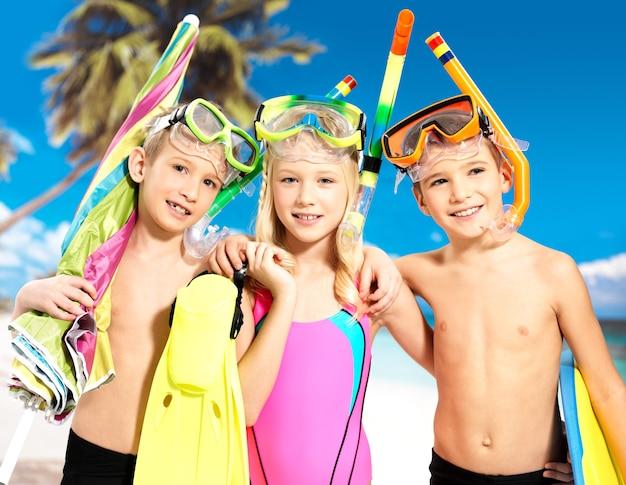 頭に水泳マスクを付けた明るい色の水着で一緒に立っている学童の子供たち。