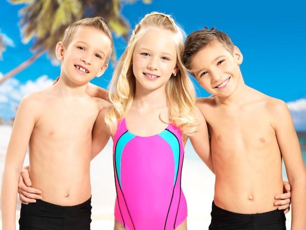 明るい色の水着で一緒に立っている学童の子供たち。