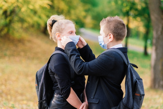 学校の子供たち、医療用マスクの男の子と女の子が都市公園を歩きます。