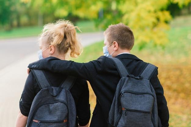 医療用マスクをかぶった少年少女の小学生が市立公園を散歩します。