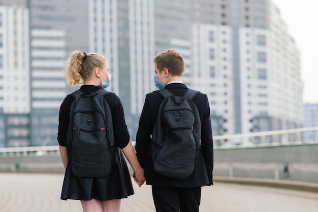 Школьники, мальчик и девочка в медицинских масках гуляют по городу.