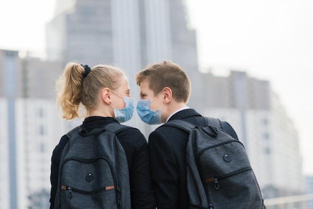 医療用マスクを身に着けた男の子と女の子の学童が街を歩きます。