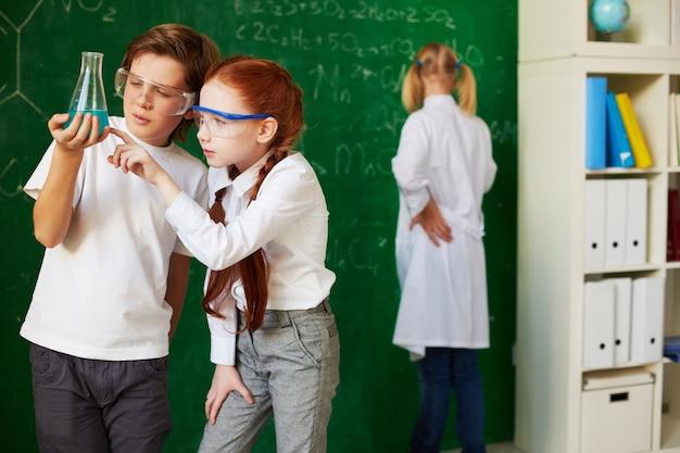 Schoolchildren analyzing a flask with blue liquid