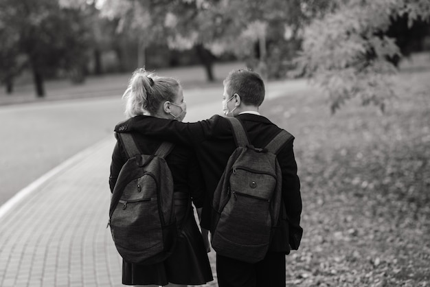 Schoolchildren, a boy and girl in medical masks walk in the city park.