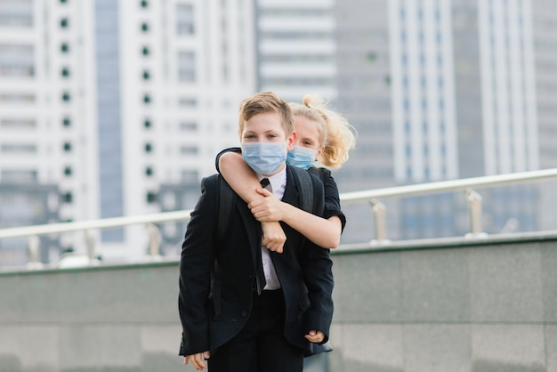 Schoolchildren, a boy and girl in medical masks walk in the city.