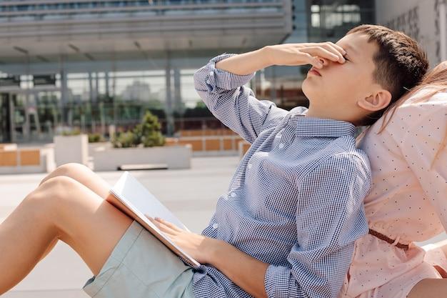 학교 운동장에서 공부하는 11세 소년 십대, 벤치에 앉아, 남학생은 피곤하다