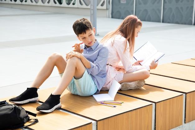 Школьники девочки и мальчики подростки 11 лет на перемене в школьном дворе читают книгу и делают домашнее задание в тетради