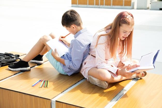 Школьники девочки и мальчики-подростки 11 лет учатся на школьном дворе, сидят на скамейке в школьном дворе, читают книгу и пишут в тетрадь