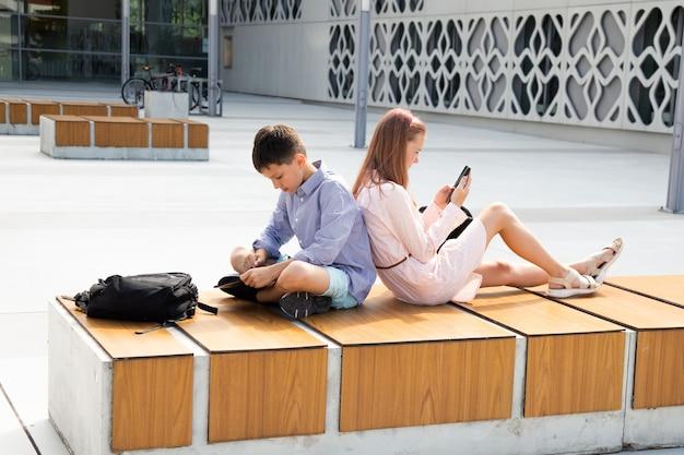 학교 운동장에서 쉬는 시간에 10대 여학생과 남학생은 벤치에 나란히 앉아 있는 동안 모바일 장치를 사용합니다.