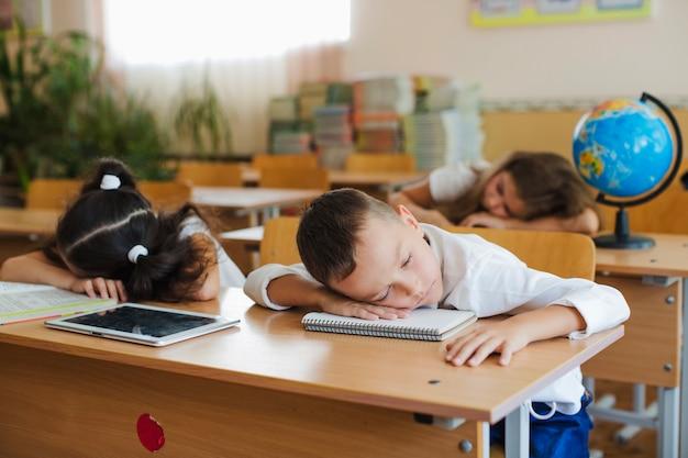 Schoolchildren leaning on table sleeping