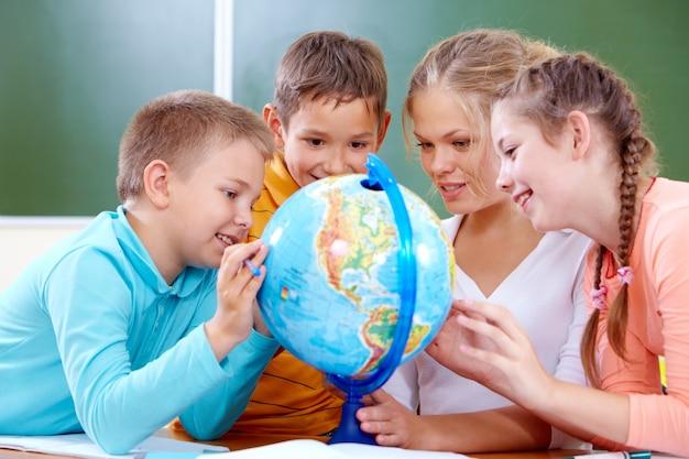 Schoolchildren learning with globe