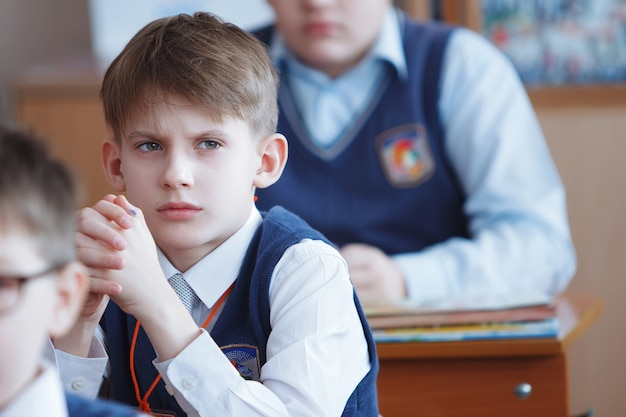 Schoolchildren on the lesson in primary school. boy looking at the teacher. education in russia. selective focus