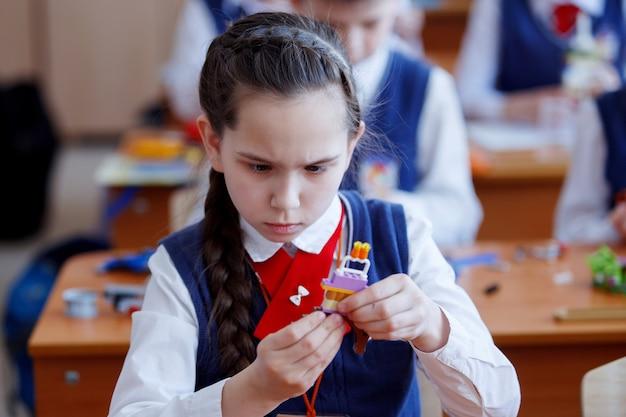 Schoolchildren play in building kit plastic blocks at a lesson in primary school