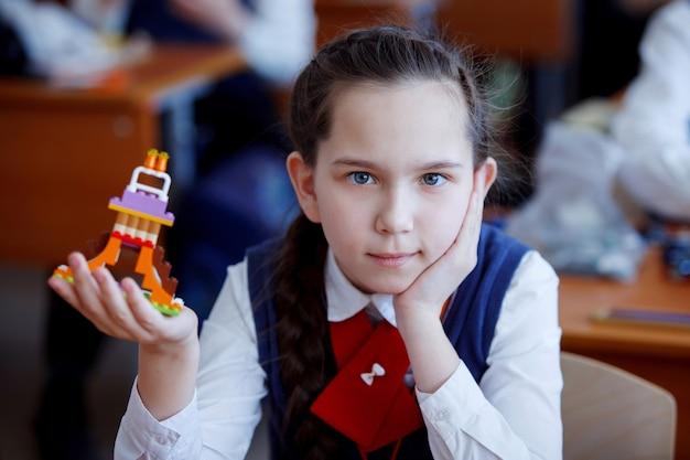 小学校の授業で、小学生がキットのプラスチックブロックを作って遊ぶ