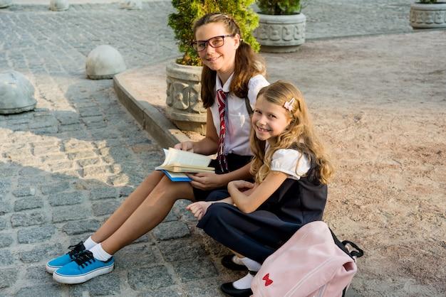 Schoolchildren reading book sitting on the sidewalk.
